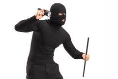 Ladro con la maschera che tiene una torcia elettrica e un pezzo di tubo Fotografia Stock