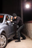Ladro con la maschera di furto che prova a rubare un'automobile Fotografie Stock Libere da Diritti