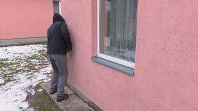 Ladro con la prova del bastone a leva alla finestra aperta stock footage