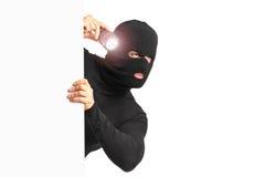 Ladro con la tenuta della torcia elettrica dietro un PA bianco Fotografia Stock Libera da Diritti