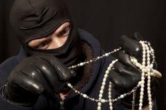 Ladro con una collana della perla Fotografia Stock Libera da Diritti