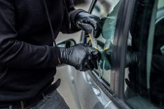 Ladrão de carro que tenta quebrar em um carro com uma chave de fenda Fotografia de Stock Royalty Free
