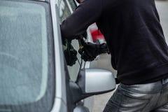 Ladro di automobile che prova a rompersi in un'automobile con un cacciavite fotografia stock