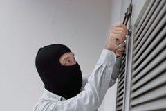 Ladro mascherato che per mezzo di uno strumento di raccolto della serratura alla violazione di domicilio con effrazione in una ca fotografia stock