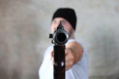 Ladro munito che indica la pistola all'obiettivo Immagine Stock