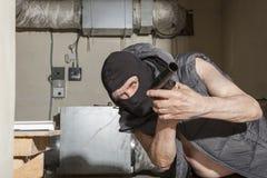 Ladro munito con una pistola nella soffitta Fotografia Stock