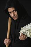 Ladro nello zoodie con la mazza da baseball ed i soldi isolati sul nero Immagini Stock