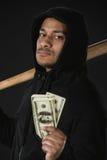 Ladro nello zoodie con la mazza da baseball ed i soldi isolati sul nero Fotografia Stock