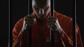 Ladro in prigione che ritiene rammarico sincero del crimine, tenente le barre della prigione in disperato stock footage