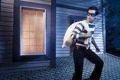 Ladro sul tetto di una casa alla notte immagine stock libera da diritti