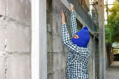 Ladro in una maschera che scala tramite un recinto immagine stock libera da diritti