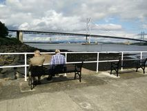 Lads at the dock. 2 friends relaxing by the sea Stock Photos