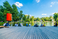 Lads and lasses have rest on the wooden deck by Golitsyn pond of Royalty Free Stock Photography