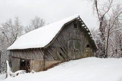 Ladugård i ett snöig landskap Arkivbild