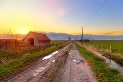 Ladugård nära Dangast på solnedgången Royaltyfri Bild