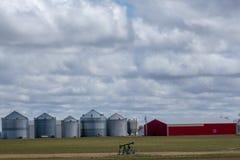 Ladugård och silor i mitt av lantgårdfältet arkivfoton