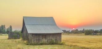 Ladugård på solnedgången Arkivfoto