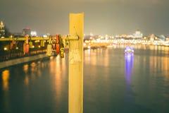 Ladugårdlås hängs på bron i heder av förhållanden och förälskelse afton royaltyfri foto