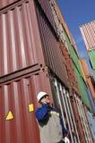 Ladungbehälter und Dockarbeitskraft Stockfotos