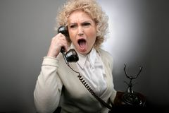 Lady 19. A senior woman with a screaming expression at  telephone Royalty Free Stock Photos