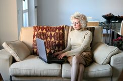 Lady 70. A senior woman at home with notebook Stock Photography