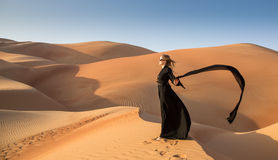 Lady in abaya in sand dunes. A woman in abaya in sanddunes in Liwa Desert, Aby Dhabi, UAE Royalty Free Stock Images