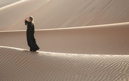 Lady in abaya in sand dunes. A woman in abaya in sanddunes in Liwa Desert, Aby Dhabi, UAE Royalty Free Stock Photos