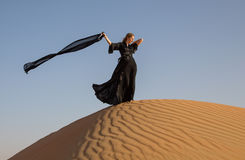 Lady in abaya in sand dunes. A woman in abaya in sanddunes in Liwa Desert, Aby Dhabi, UAE Royalty Free Stock Photo