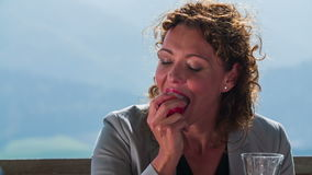 Lady agrees with business partners. Slow motion close-up footage of a beautiful business woman picking up the apple in the middle of the nice landscape on sunny stock footage