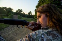 Lady aiming shotgun stock photography
