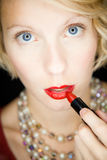 Lady with amazing eyes putting lipstick (like in front of a mirror) Royalty Free Stock Image