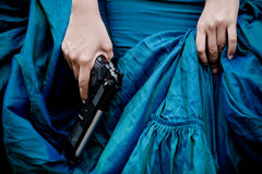 Lady assassin. Close up photo of female assassin wearing blue gown Stock Images