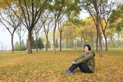Lady in autumn. The Chinese woman was sitting in autumnal forest stock images