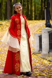 Lady in autumn forest. Lady in medieval red dress in the autumn forest Royalty Free Stock Image