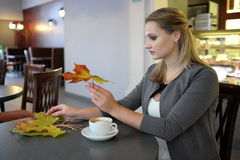 Lady - Autumn indoor portrait in a cafe. Attractive young woman with colour leaves sitting in a cafe with a cup of coffe closeup portrait Royalty Free Stock Photography
