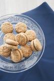 Lady& x27 ; baisers de s et x28 ; pâtisseries de pâtisserie avec l'amande et le chocolate& x29 ; sur le gâteau en verre se tient  Photographie stock libre de droits