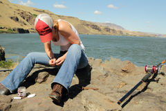 Lady Baiting a Fishing Pole. Lady baiting a hook and fishing for sturgeon on the Columbia River in Eastern Washington with view of territory under clear blue Royalty Free Stock Photography