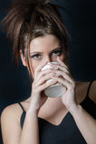 Lady with bangs holding a cup Royalty Free Stock Image