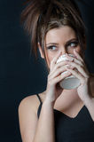 Lady with bangs holding a cup Royalty Free Stock Images