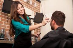 Lady barber cutting hair Stock Photos