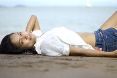 Lady on the beach. Pretty girl in casual clothes laying on the beach Royalty Free Stock Images