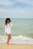 Lady on the beach. Beautiful asian lady wearing white shirt walking on the beach royalty free stock photo