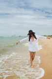 Lady on the beach. Beautiful asian lady wearing white shirt walking on the beach royalty free stock images