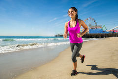 Lady on beach blue skies run jog fitness athlete weight training endurance runner pier ocean Royalty Free Stock Photos