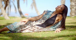 Lady in Beach Dress Relaxing at Grassy Ground stock video footage