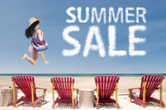 Lady at beach with summer sale cloud. Young lady wearing bikini, jumping at beach with summer sale cloud and beach chairs stock images