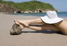Lady on beach white hat and feet on coconut. Woman resting legs on coconut on tropical beach with white hat on knee, guanacaste, costa rica, central america Royalty Free Stock Photo
