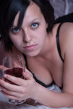 Lady at bed holding a glass of red wine Stock Images