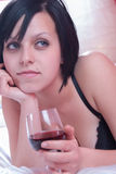 Lady at bed holding a glass of red wine Stock Photo