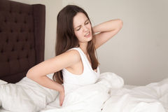 Lady in bed suffering from backache after sleep. Young woman sitting in bed stretching and rubbing stiff back muscles after waking up in morning. Lady suffering Royalty Free Stock Photo